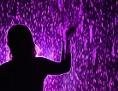 Eine Frau streckt die Hände in die Höhe, man sieht nur ihren Schattenriss in einem dunklen, violetten Raum