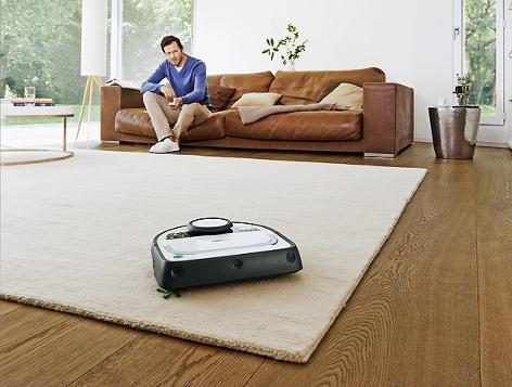 Staubsauger-Roboter fährt über Teppich, ein Mann sitzt im Hintergrund mit Fernbedienung auf dem Sofa
