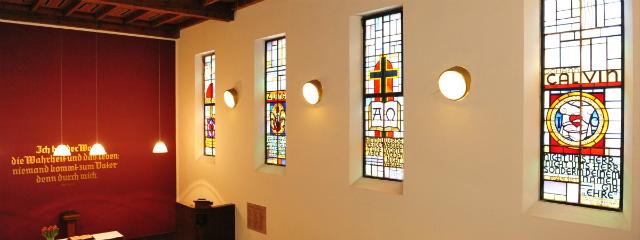 Kirche innen mit Bibelspruch an der Wand über dem Altar und vielen hinterglasbemalten Fenstern