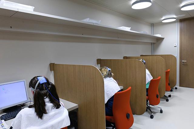 Probandinnen tragen Kappen mit Elektroden und sitzen in Kojen vor einem PC