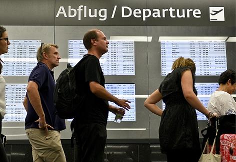 Flugpassagiere vor den Check-In Schaltern des Flughafen Wien-Schwechat
