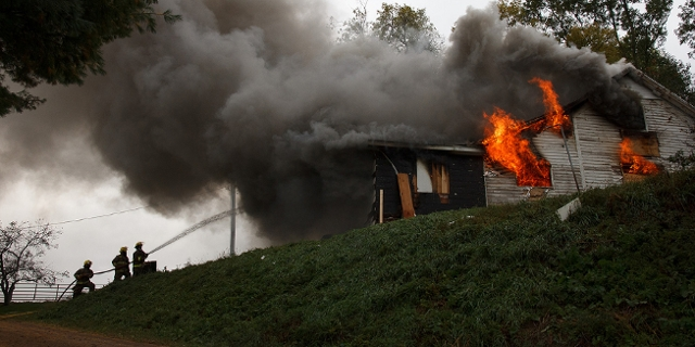 Ein brennendes Haus, das von der Feuerwehr gelöscht wird.