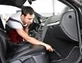 Mann saugt sein Auto