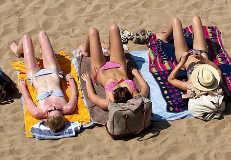 Drei Frauen sonnen sich am Strand, eine davon ist schon ganz rot auf der Haut