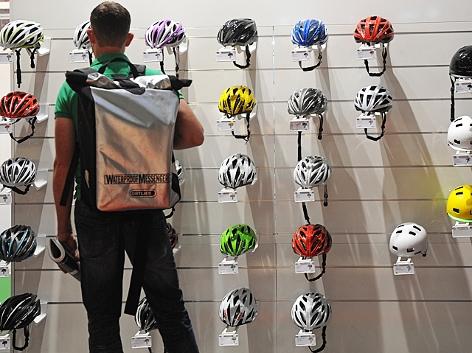 Ein Mann steht vor einer Wand mit Fahrradhelmen