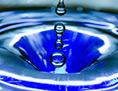 Ein Wassertropfen fällt in eine blaue Wasserschüssel