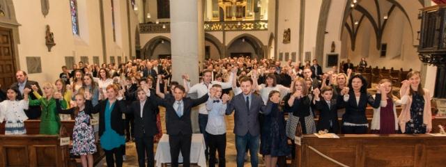 Kirchentotale mit Jugendlichen in einem Festgottesdienst halten sich bei erhobenen Händen