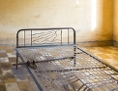 Ein altes Bett ohne Matratze in einem fast leeren Raum