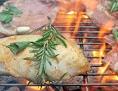 Schweinekotletts und Hühnerbrust auf dem Griller