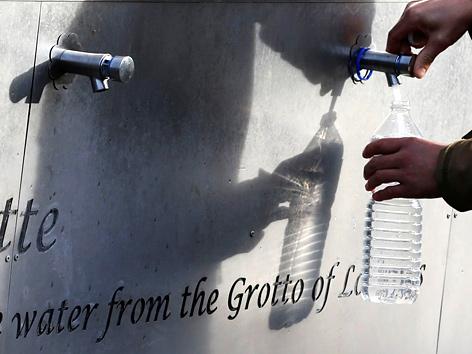 Ein Pilger füllt Wasser in seine Flasche in Lourdes