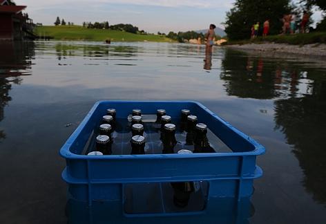 Eine Bierkiste steht zur Abkühlung im See