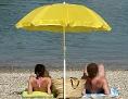 Ein Mann und eine Frau am Strand bei großer Hitze unter einem gelben Sonnenschirm