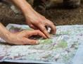 Erwachsene mit Landkarte im Wald