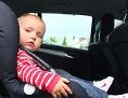 Ein kleines Mädchen sitzt in ihrem Autokindersitz