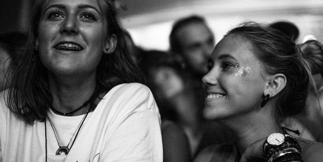Zwei junge Frauen mit Glitzer im Gesicht im Publikum
