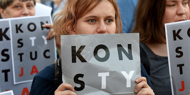 "Protesters hold posters reading ""constitution"" during a protest in front of the presidential palace in Warsaw"