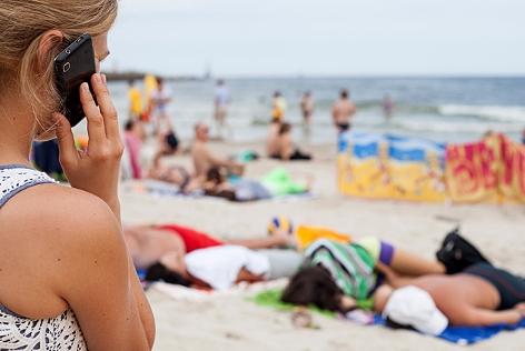 Eine Frau telefoniert mit einem Mobiltelefon am Strand