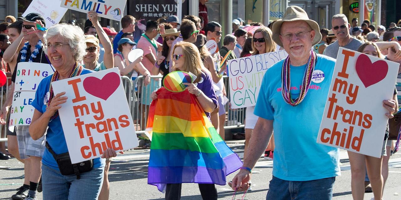 Eltern mit Schildern bei einer Pride Veranstaltung