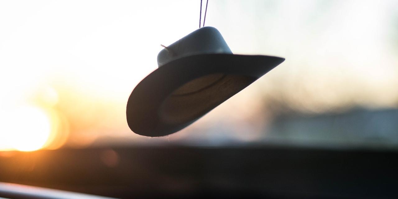 Ein Hut, der hinter einer Auto-Windschutzscheibe hängt.