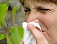 Eine Frau niest in ein Taschentuch