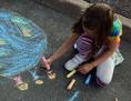 Ein Kind malt mit Straßenmalkreide