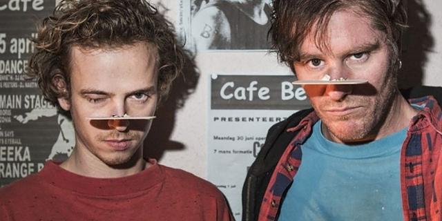 """Zwei Männer vor einer Plakatwand, Szenenbild aus """"Belgica"""""""