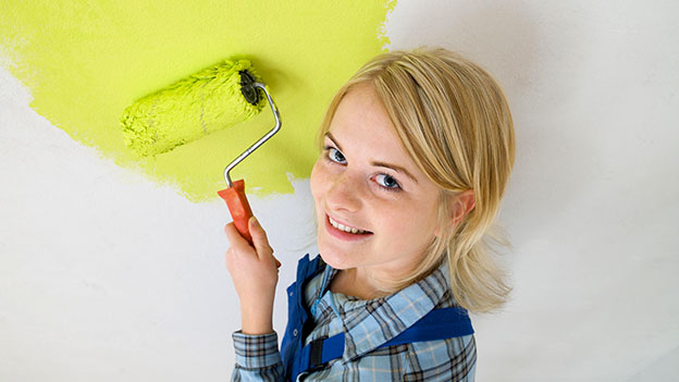 Frau malt Wand giftgrün an