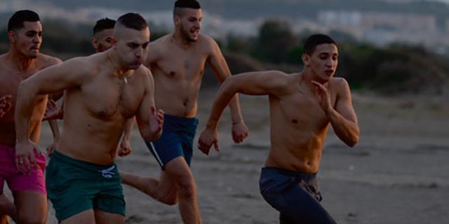 Viele junge Männer laufen über einen Sandstrand