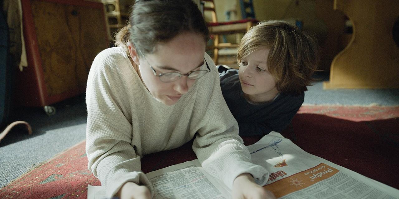 """Filmstill """"Die beste aller Welten"""" Kind und Mutter liegen am Boden und lesen Zeitung"""