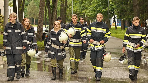 8 Junge Feuerwehrleute in Uniform und mit Helmen in der Hand kommen auf den Betrachter zu
