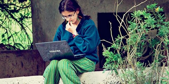 Frau sitzt auf Mauer im Grünen mit Laptop