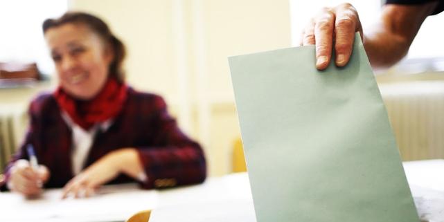 Umschlag, der in Wahlurne gesteckt wird