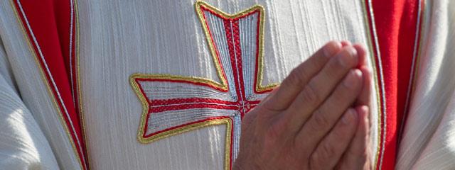Gefaltete Hände eines Bischofs