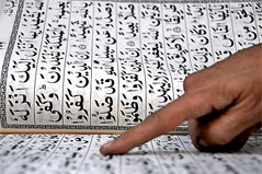 Finger zeigt auf Koranverse