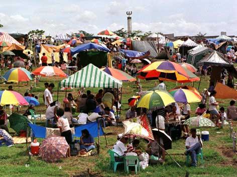 Ein Militärfriedhof in Manila wird zu Allerheiligen von Menschen mit Tischen und Sonnenschirmen besucht.