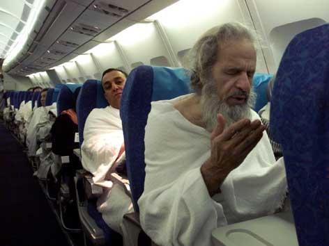 Muslime beten in einem Flugzeug.