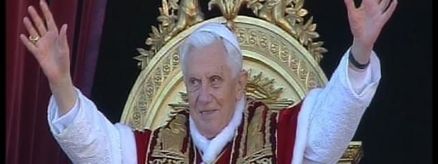 Papst Benedikt XVI. hebt grüßend und lächelnd die Hände