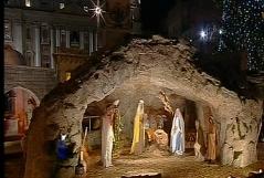 Krippe am Petersplatz nachts mit funkelndem Weihnachtsstern und hell erleuchtetem Christbaum