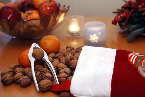 Nikolausgaben: Mandarinen, Nüsse, Äpfel neben Kerzen