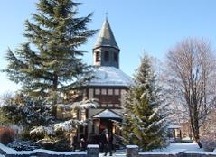 Evangelische Heilandskirche Dornbirn mit Gemeinde vor dem Kirchentor, im Winter bei Tag