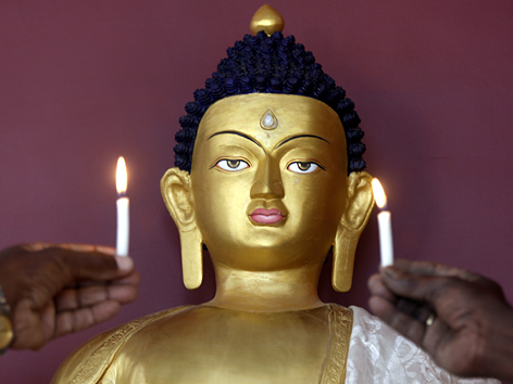 Buddha-Statue mit Kerzen davor