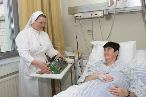 Ordensschwester mit Patientin in Krankenzimmer