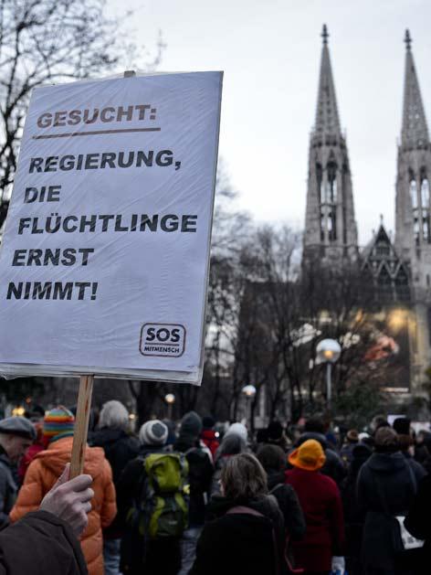 """Demonstranten vor der Votivkirche mit einem Plakat mit der Aufschrift """"Gesucht: Regierung, die Flüchtlinge ernst nimmt""""."""