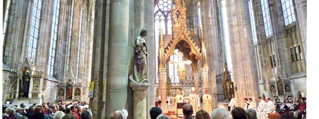 Menschen während der Messe in der Stiftskirche Heiligenkreuz vor dem Altar unterm Kreuzgewölbe