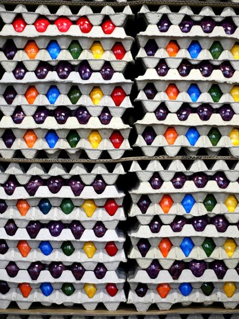 Gestapelte Kartons mit gefärbten Eiern in verschiedenen Farben