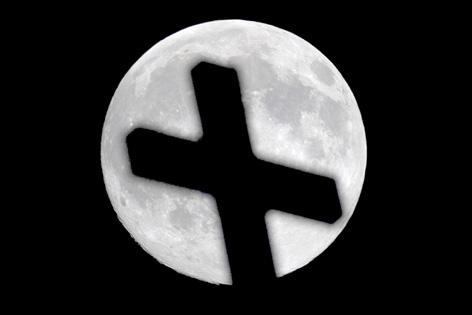 Die Silhouette eines Kreuzes vor dem Vollmond