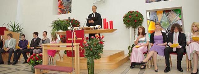 Altarraum mit jungen Gemeindegliedern und Pfarrer Heiner Schmidt