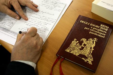 """Ein Buch mit dem Titel """"Ritual für den Exorzismus und Gebete für besondere Umstände"""" (italienisch) liegt auf einem Tisch. Daneben macht sich jemand Notizen."""