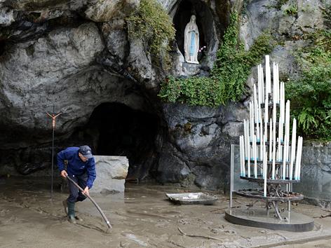 Aufräumarbeiten nach Überschwemmung vor der Grotte in Lourdes im Oktober 2012