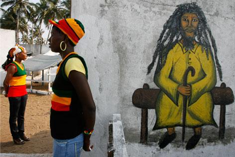 Zwei Rasta-Frauen neben einem Wandbild, das einen alten Rastafari auf einer Bank sitzend darstellt